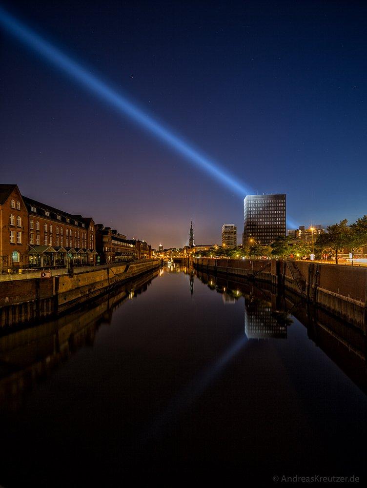 """Lichtstrahl von """"Crossing The Elbe"""" über dem Zollkanal in der Hamburger Speicherstadt."""